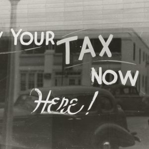 photo -- old timey window with Pay Your Tax Now Here written on it