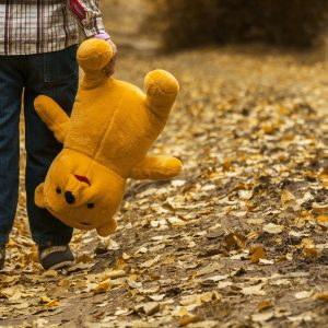 child carrying stuffed bear